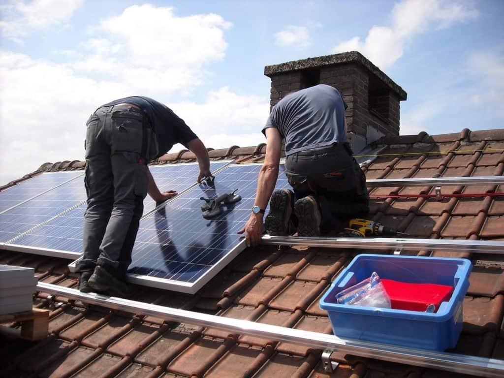 בעלי מקצוע מתקינים פאנלים סולרים על הגג